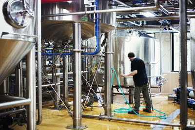 Man working in a brewery, connecting a hose to a metal beer tank.