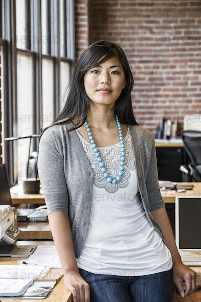 Asian woman at her creative office work station.
