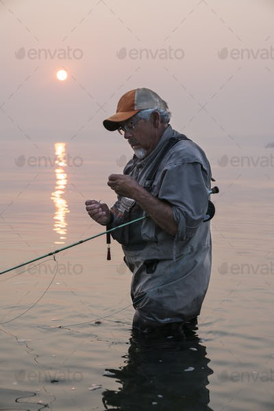 Man tying a fly on his fly fishing line while fishing for salmon and searun cutthroat trout in Puget