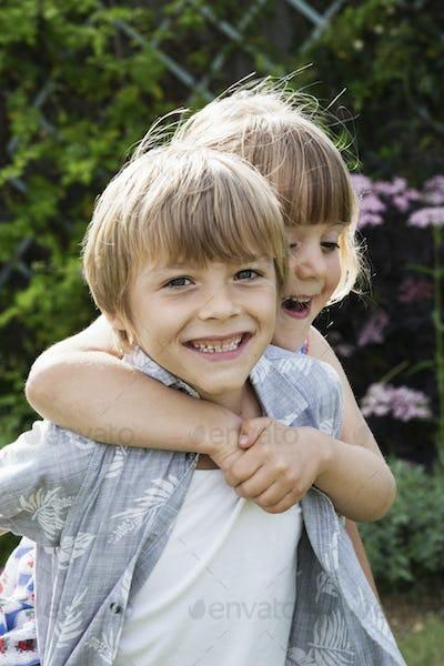 Girl hugging a smiling boy, looking at camera.