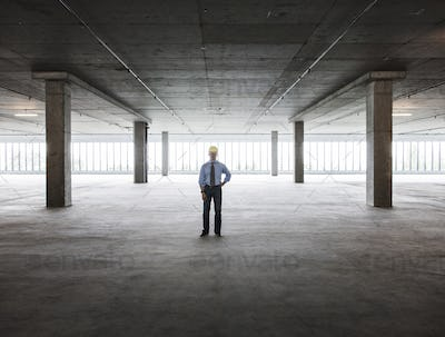 Asian businessman in a new empty raw office space.