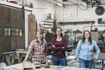 Three women standing in metal workshop, holding looking at camera.
