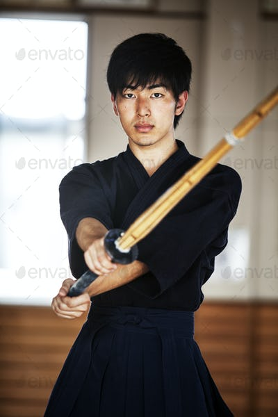 Male Japanese Kendo fighter holding wood sword in combat pose, looking at camera.