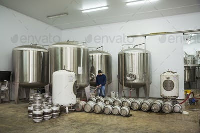 A man filling metal beer kegs from large fermentation tanks in a brewery.