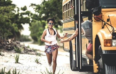 A young woman chasing after a moving school bus.
