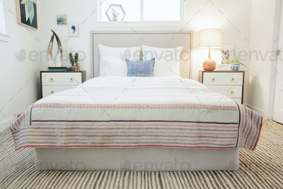 A bedroom in an apartment with a double bed and a retro look antique patterned patchworked bed