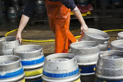 Man working in a brewery, holding metal beer kegs.