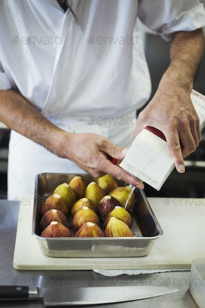 High angle close up of chef working in the kitchen of a Japanese sushi restaurant, preparing figs in