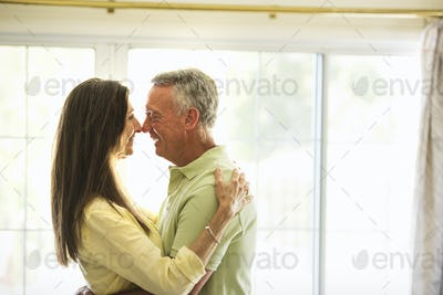 Senior couple standing indoors, embracing.