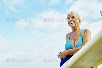 Smiling senior woman wearing a bikini and wetsuit standing net to a surfboard.