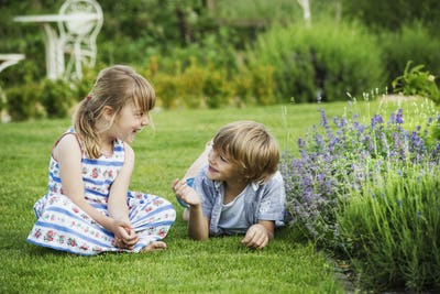 A girl sitting on the grass talking to her brother lying beside her on a lawn in a garden.