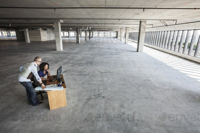 Black business woman and Asian business man working on a computer at a desk in a large new empty