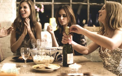 A group of women at a party, pouring and drinking champagne.