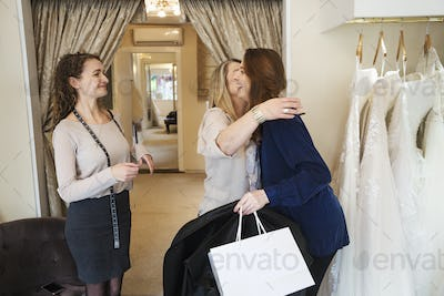 Three women in a wedding dress shop, one hugging and greeting a customer. A bridal boutique.