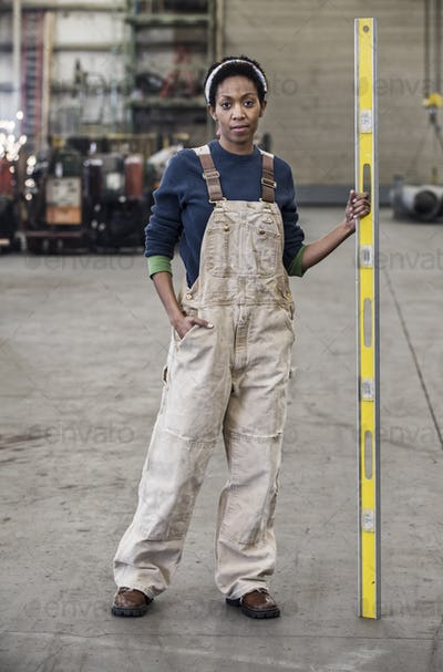 Black woman factory worker standing on the floor of a sheet metal factory.