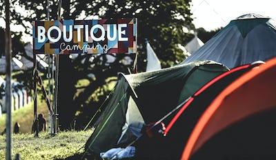 Tents on grass in a camping area at an outdoor music festival in summer.  Sign reading Boutique