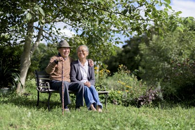 Husband and wife, elderly man wearing hat and woman sitting side by side on a bench in a garden.