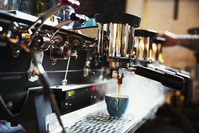 Specialist coffee shop. A coffee machine making coffee. Steam and heat.