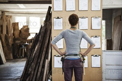 Woman factory worker checking project inventory in a woodworking factory.