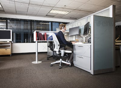 Caucasian businessman working at his computer while sitting in his cubicle office.