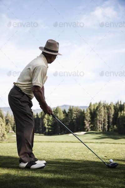 Senior golfer teeing off during a round of golf.