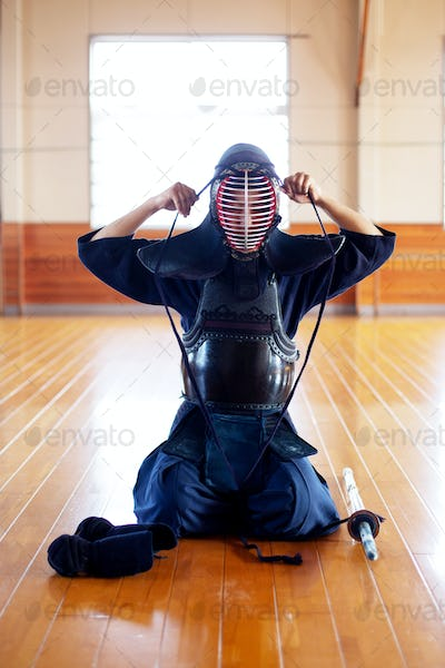 Female Japanese Kendo fighter kneeling on wooden floor, fastening Kendo mask.