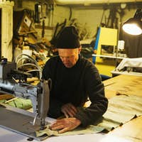 Man in a sailmaker's workshop sewing a sail with a sewing machine.
