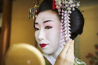 A woman made up in the traditional geisha style, with an elaborate hairstyle and floral hair clips,