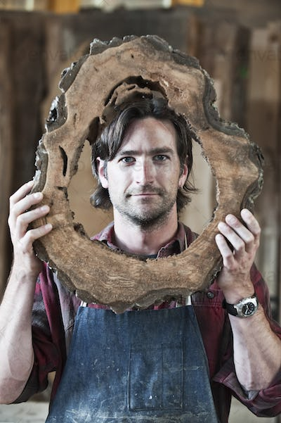Caucasian man factory worker holding a cut piece from a section of a reclaimed recycled tree in a