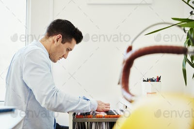 A man looking in a filing cabinet drawing, sorting through hanging files.