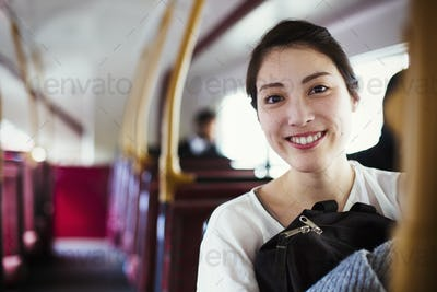Young Japanese woman enjoying a day out in London, riding on a double decker bus.
