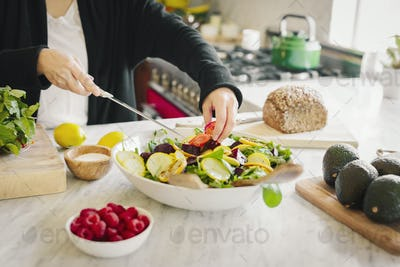 A woman in a kitchen preparing a salad dish with fresh vegetables.