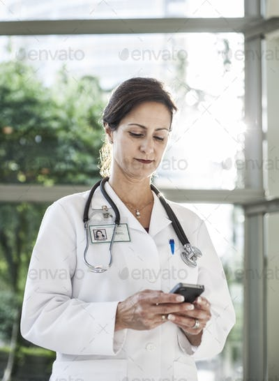 Caucasian female doctor in lab coat with stethescope.