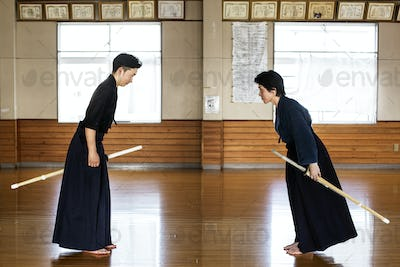 Female and male Japanese Kendo fighters standing opposite each other on wooden floor, bowing and