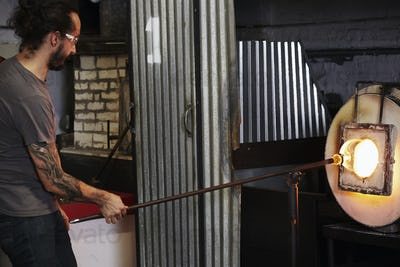 A glassblower holding a piece of molten glass to the furnace to heat it up.