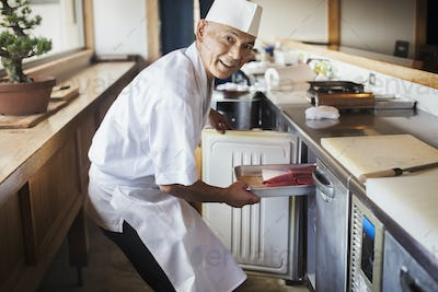 Chef working at a counter at a Japanese sushi restaurant, putting metal tray with fish in