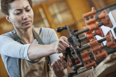 Black woman factory worker adjusting clamps while glueing a large wooden part in a woodworking