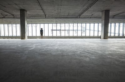 Business woman standing near windows in a new empty raw office space.