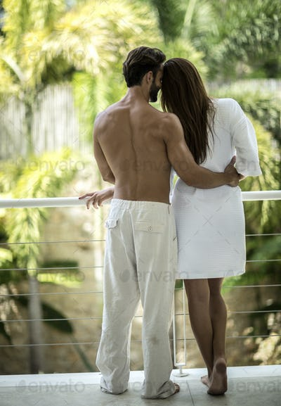 A rear view of a couple standing on a balcony hugging.