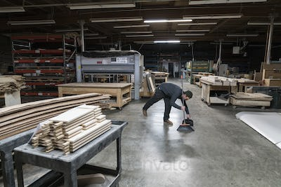An employee sweeping up after work hours in a large woodworking factory.