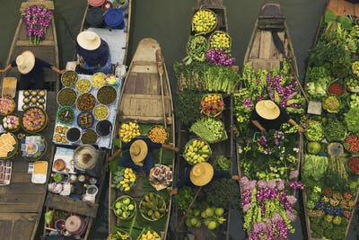 Aerial view of a floating market on a canal in Bangkok, local boats laden with fresh food, moored