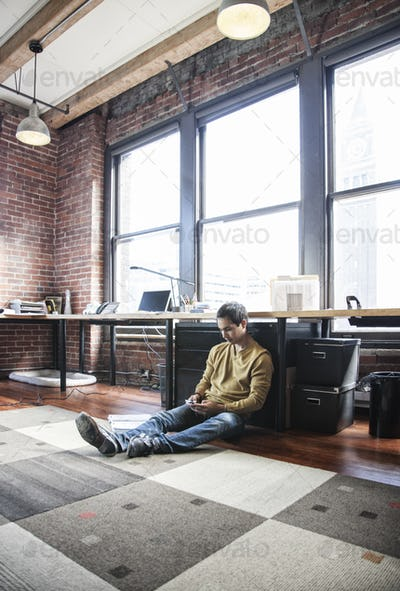 Hispanic man on his cell phone while sitting on floor at his office workstation.