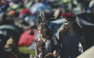 Two smiling young women at a summer music festival face painted, wearing feather headdress, standing