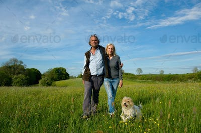 Man and woman walking arm in arm across a meadow, small dog running beside them.