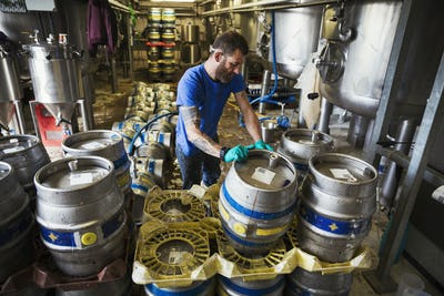 Man working in a brewery, stacking metal beer kegs.