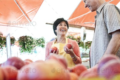 Smiling woman wearing apron and man standing at stall with fresh peaches at a fruit and vegetable