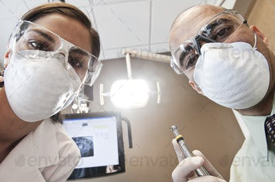 Looking up at a male dentist and a female technician from the viewpoint of a patient.