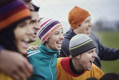 Group of men and women friends cheering at an informal sporting event in winter.