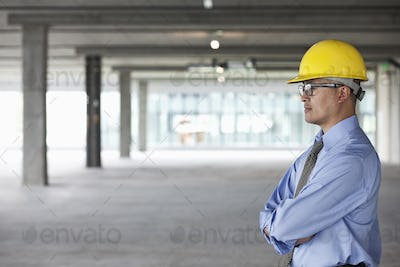 Asian businessman taking a look at a large empty raw office space.