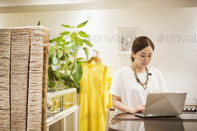 Woman working in a fashion boutique in Tokyo, Japan, working on laptop computer.